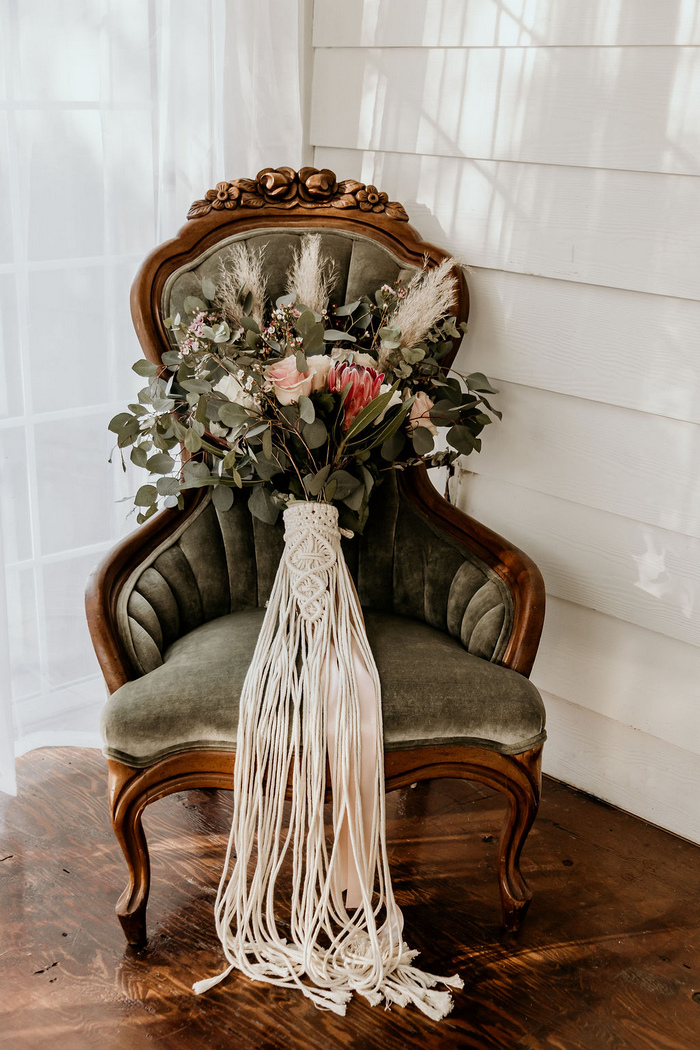The wedding bouquet was a lush arrangement with waxflowers, roses, king proteas, eucalyptus and a macrame wrap