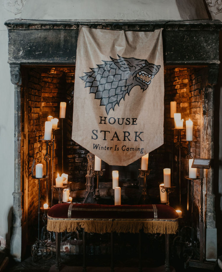 What a gorgeous ceremony space with an antique fireplace with candles and a Stark flag