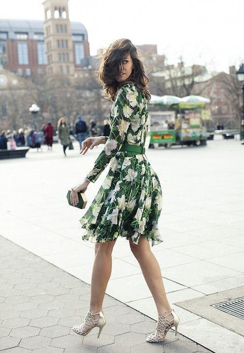 a floral long sleeve over the knee dress in green and white, a green belt, silver laser cut shoes and a small geometric clutch