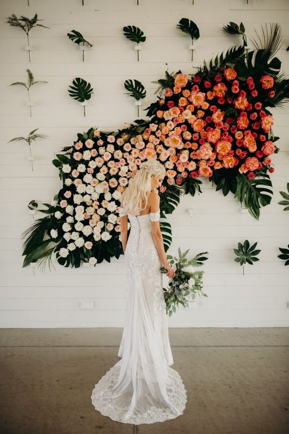 a lush ombre floral and tropical leaf wedding installation as a wedding backdrop for a wow effect