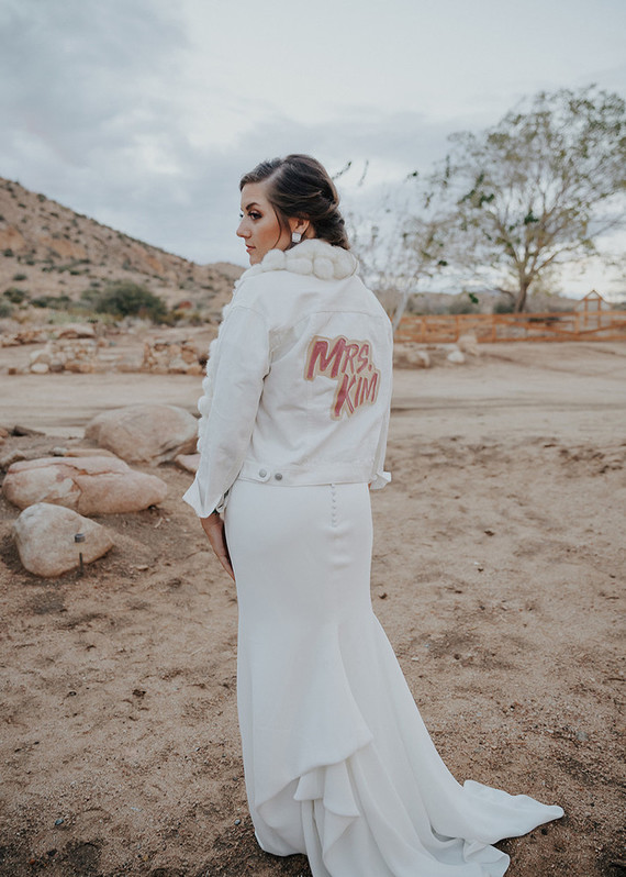 The bride was wearing a white denim jacket with pompoms and a painted back