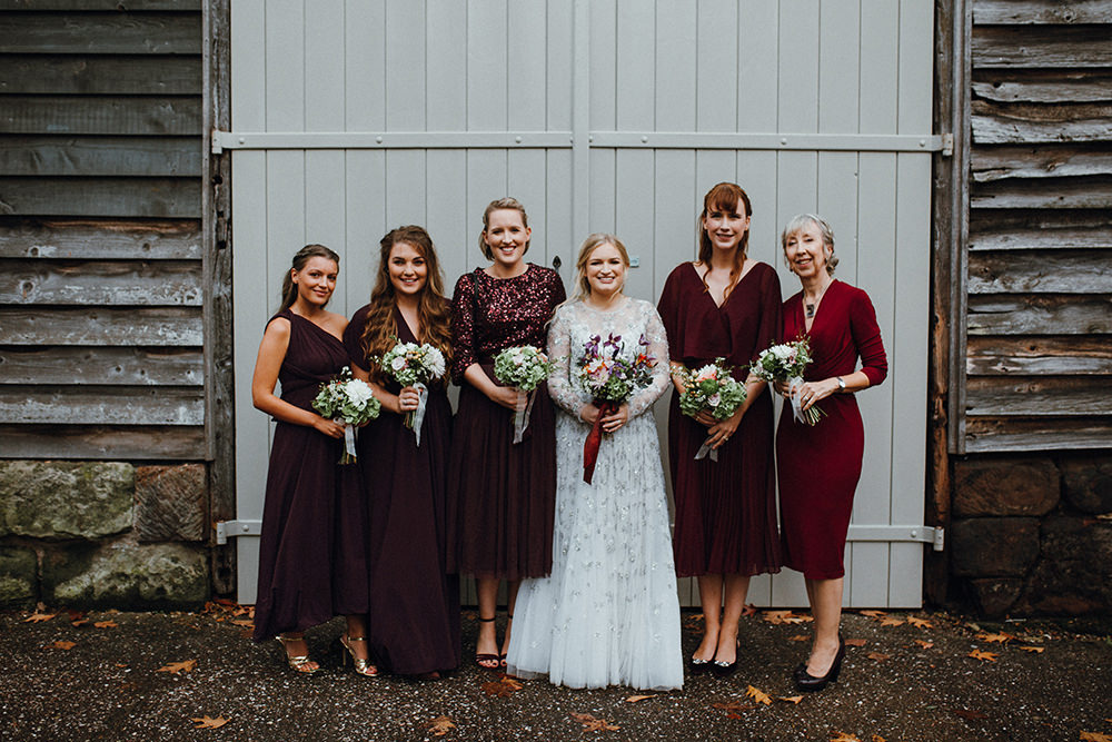 The bridesmaids were wearing mismatching burgundy and fuchsia dresses