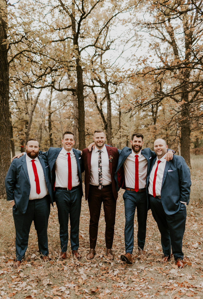 The groom was wearing a burgundy suit with a moody floral tie, the groomsmen opted for grey suits and red ties