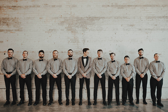 The groom was wearing a grey tux with black lapels and the groomsmen were wearing grey shirts with black pants and bow ties