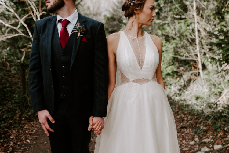 The groom was wearing a navy checked three-piece suit and a burgundy tie plus a boutonniere