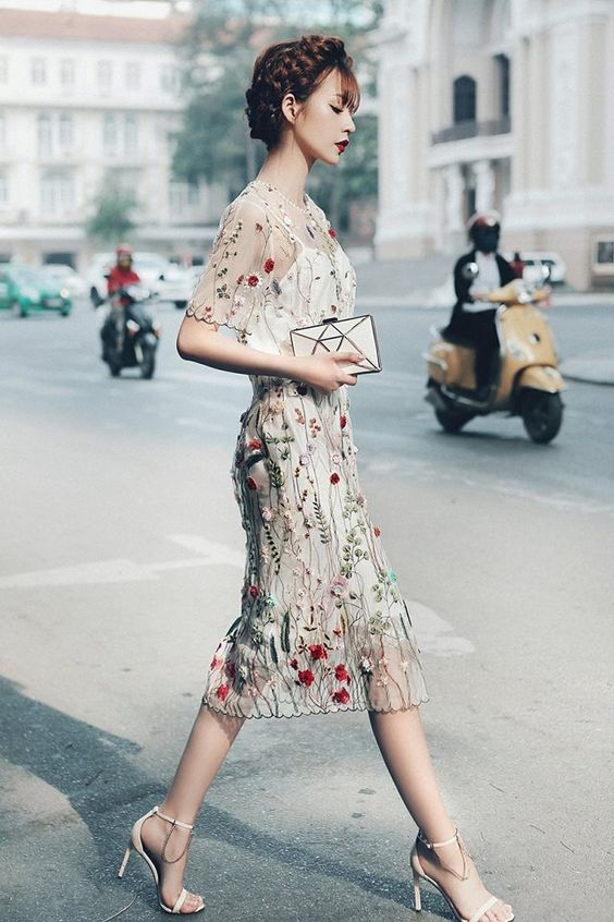 a floral embroidery and applique midi fitting dress with short sleeves, cremay heels with chains and a geometric clutch