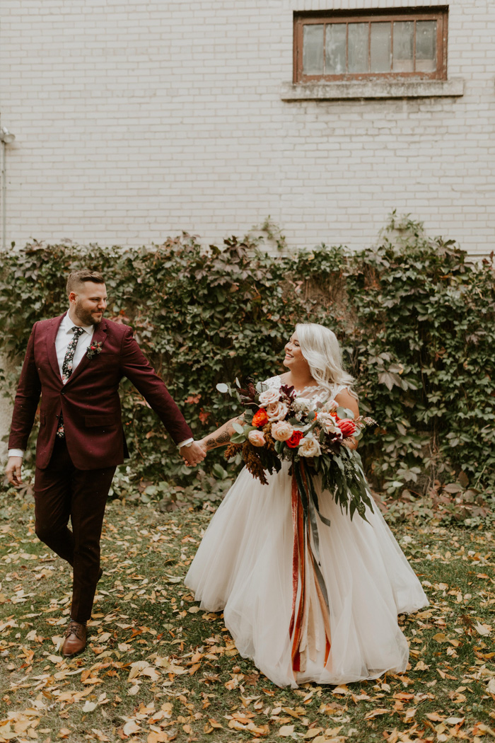 The bride was carrying a lush and bright wedding bouquet with red and pink blooms and ribbons