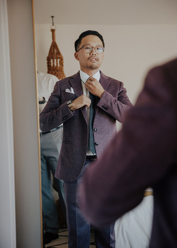 The groom was wearing a muted purple suit with a blue tie and a white button down