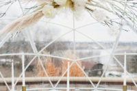 05 The wedding tablescape was done with powder blues, a pampas grass and blooms overhead installation, brass touches and candles