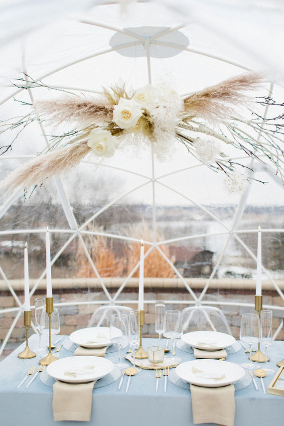 The wedding tablescape was done with powder blues, a pampas grass and blooms overhead installation, brass touches and candles