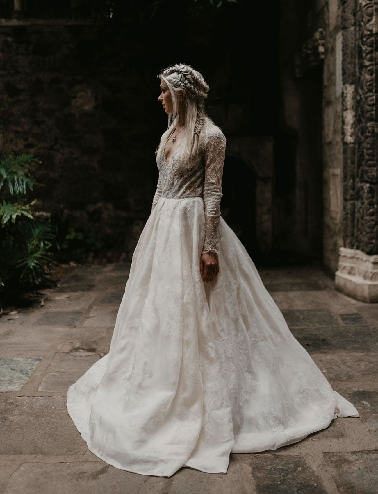 The bride was rocking a lace A line wedding dress with long sleeves and a double braided halo half updo