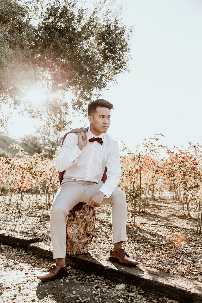 The groom was wearing tan pants, a white shirt, brown shoes, a burgundy bow tie and a pink blazer