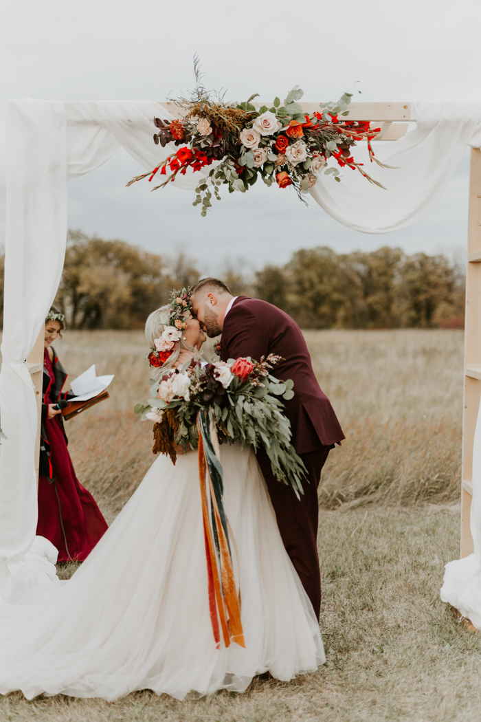 The wedding arch was done with airy neutral fabric and lush blooms on top