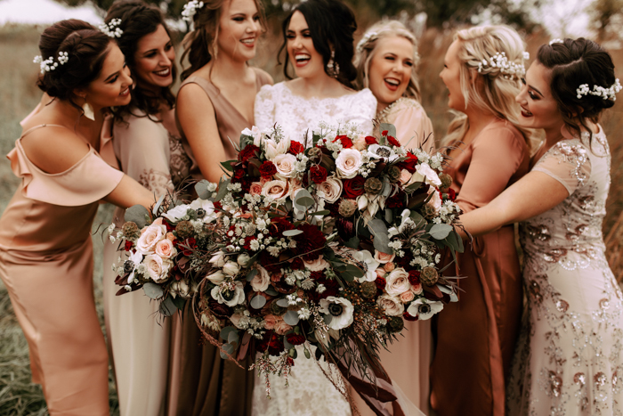 The wedding bouquets were done with neutral and deep red blooms plus lush greenery