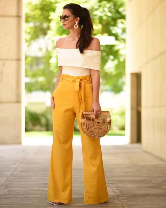 high waisted yellow pants, a creamy off the shoulder top, a straw bag and statement earrings