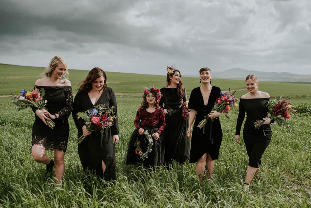 The bridesmaids were wearing mismatching black dresses