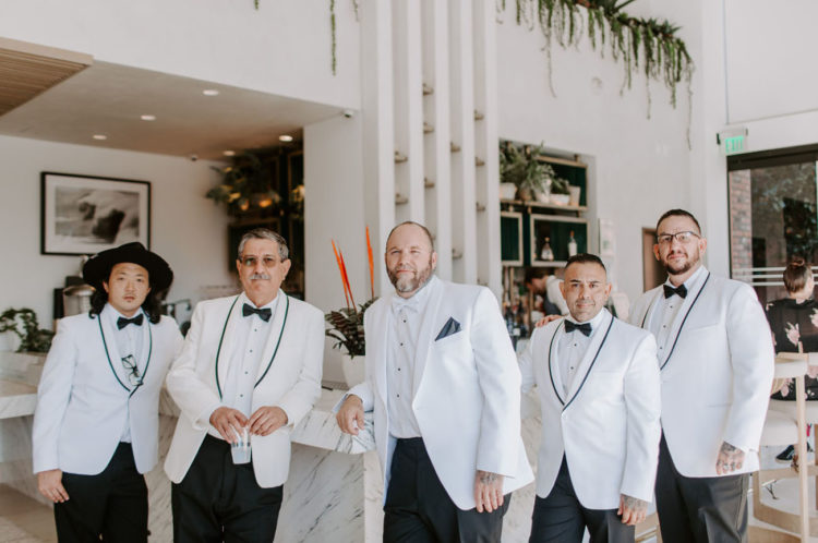The groom and groomsmen were wearing white tuxedos