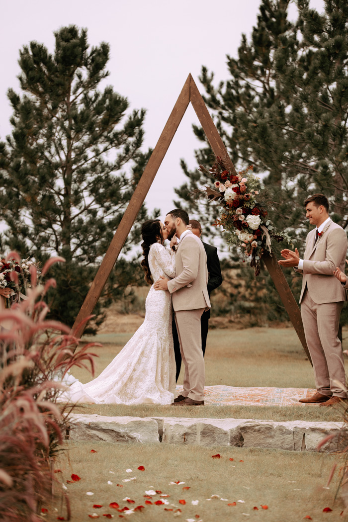 The wedding arch was a triangle decorated with deep red and neutral blooms plus greenery