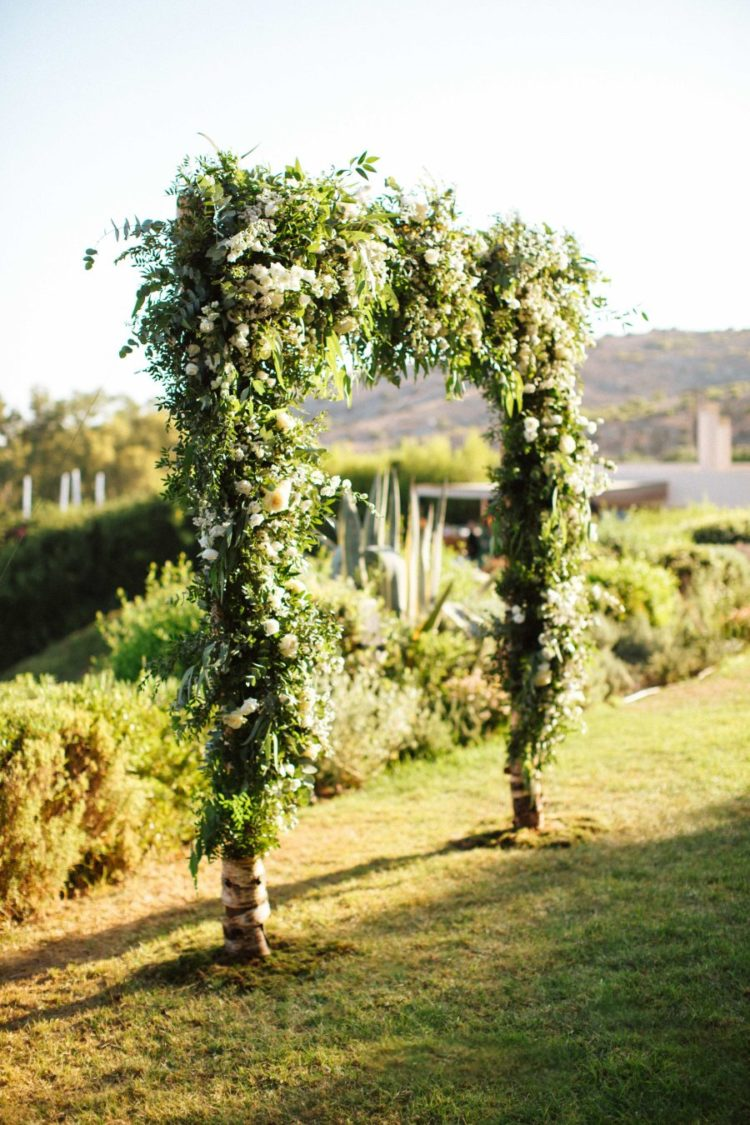 The wedding arch was made of branches, lush textural greenery and neutral blooms