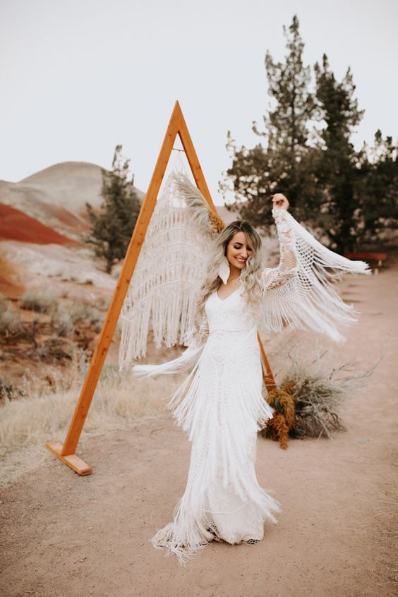 a lace wedding gown decorated with long fringe on the sleeves and on the skirt for a wild look