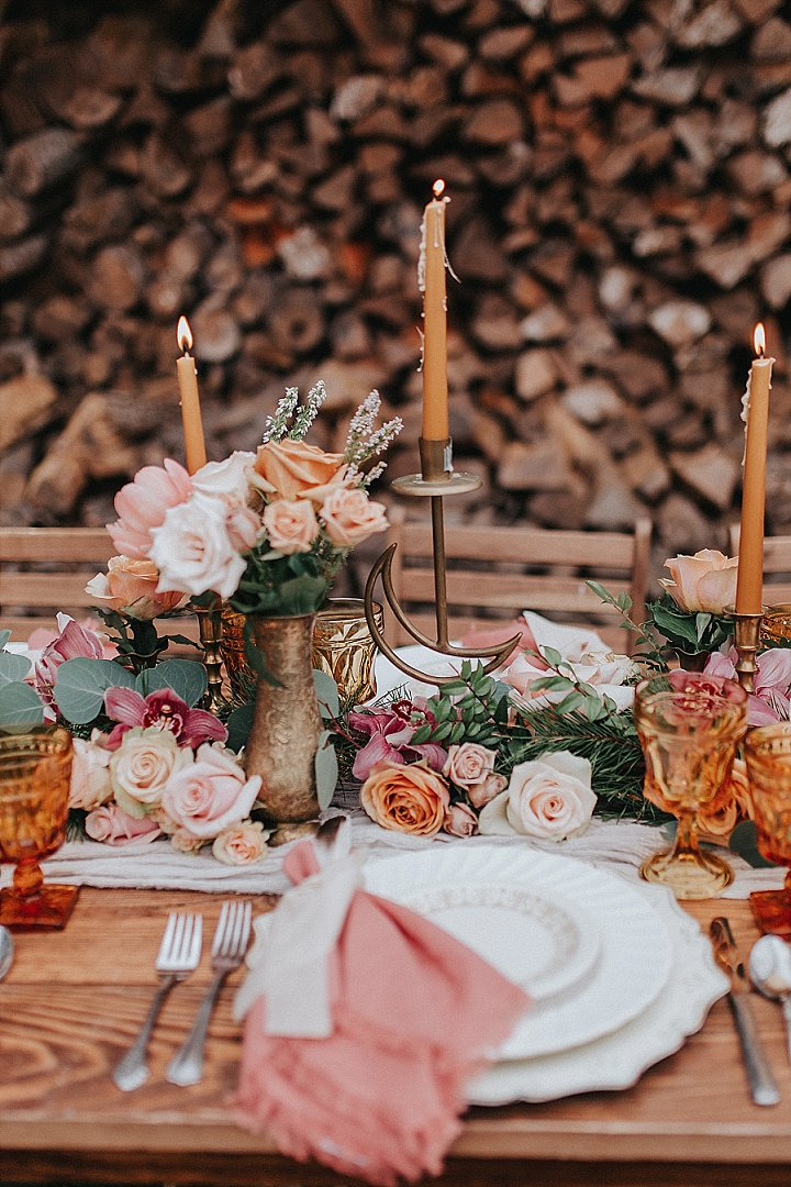 A neutral fabric table runner was paired with a lush greenery and pink bloom one plus camel candles