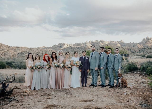 The bridesmaids were wearing mismatching blush and grey maxi gowns and the groomsmen were wearing grey suits