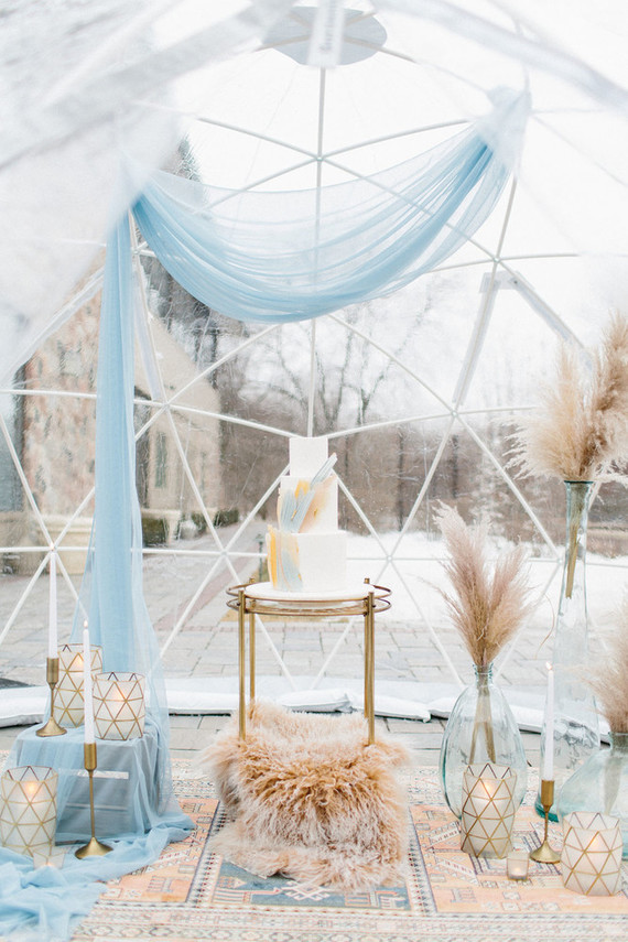 The cake was displayed with light blues, pampas grass, faux fur and geometric candle holders