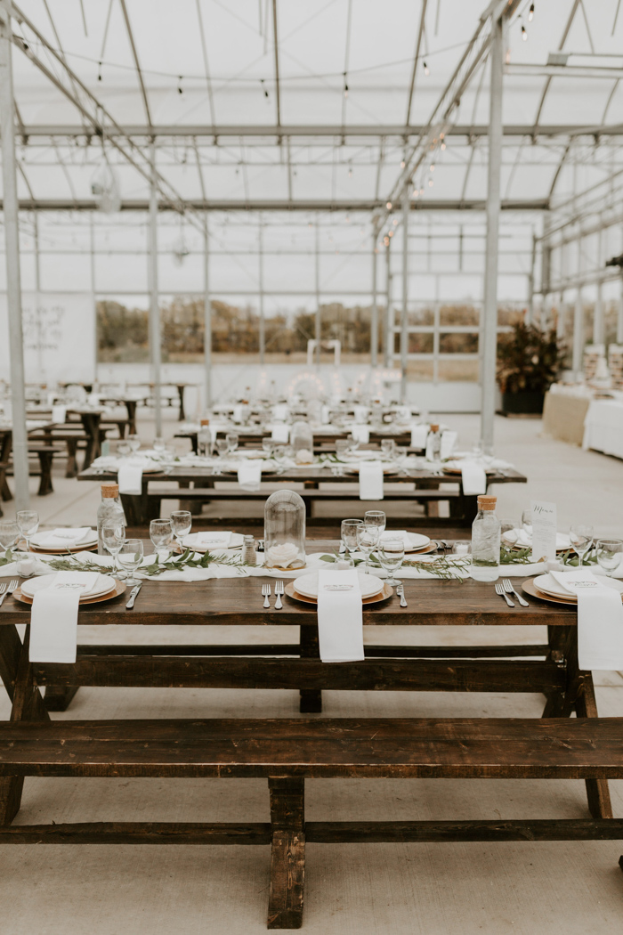 The reception tables were styled with airy fabric runners, greenery, white roses in cloches