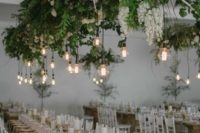 08 a lush greenery and white bloom installation with bulbs hanging down is a bold modenr decor idea