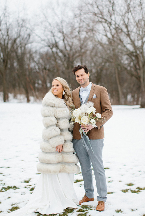 The bride covered up with a stylish faux fur coat for the outdoor shots