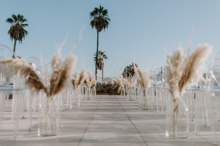 The ceremony space was done with ghost chairs and a vase with pampas grass