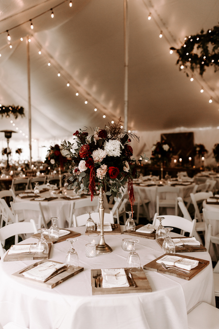 The wedding reception tables were done with white tablecloths, bright floral cennterpieces on stands and wooden placemats