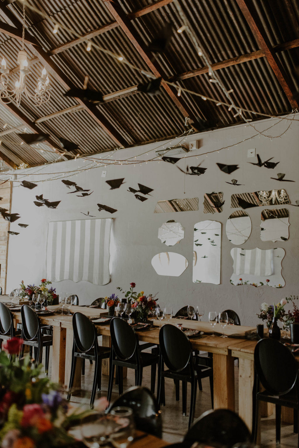 The wedding reception was done with uncovered tables and black chairs, with lush and bright florals