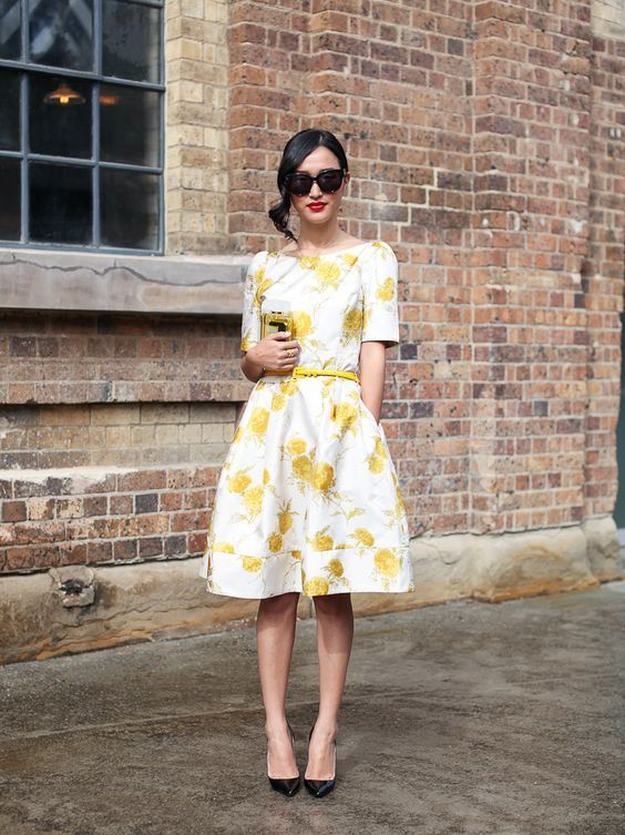 a floral A-line knee dress with a thin yellow belt and black heels for a refined look