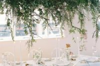 09 a lush greenery and white bloom wedding installation over the reception table for a refershing spring feel