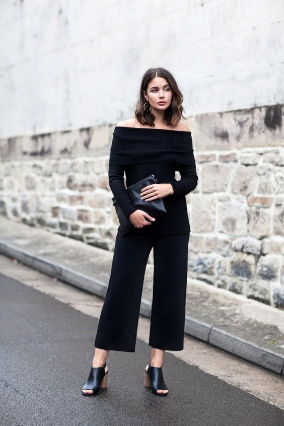 black culottes, a black strapless top with long sleeves, a black clutch and black mules