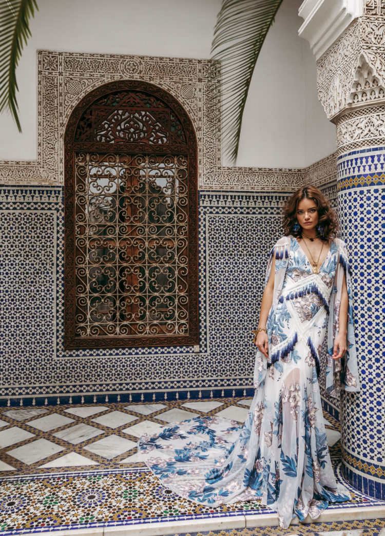 Aegean wedding dress by Rue de Seine done with blue embroidery and tassels, with a train