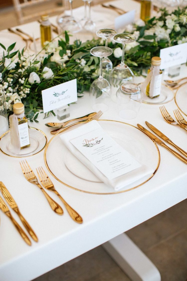 The wedding tablescape was neutral, with gold cutlery, with a greenery and white bloom table runner plus olive oil favors