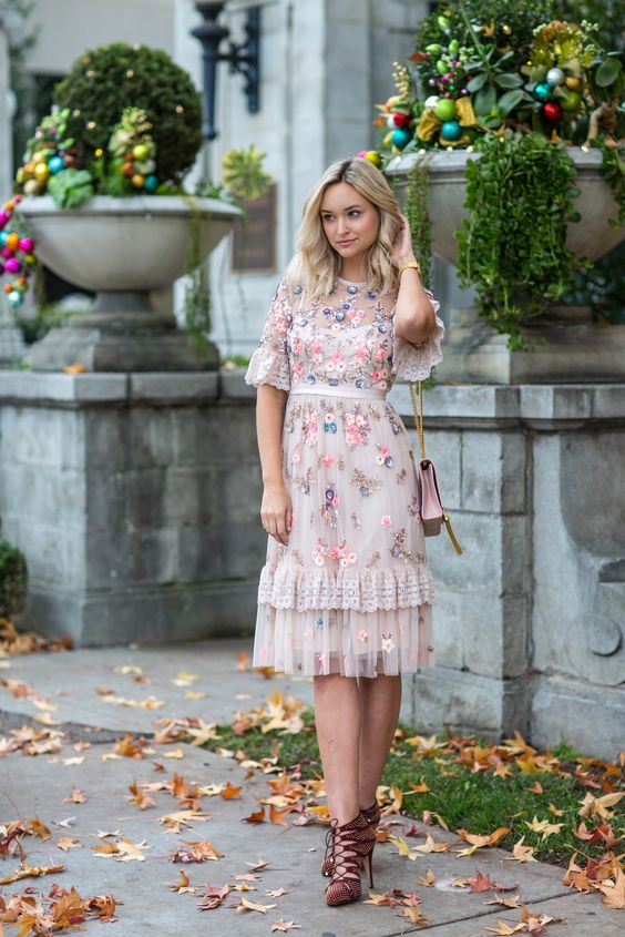 a knee floral embroidery dress with short sleeves and ruffles, a pink bag and burgundy lace up heels