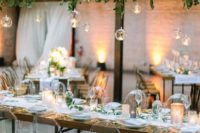 10 a lush greenery installation with hanging bubbles and candles is a very refreshing idea for an indoor wedding