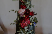 11 A textural black wedding cake with lush and bright florals was create by the bride