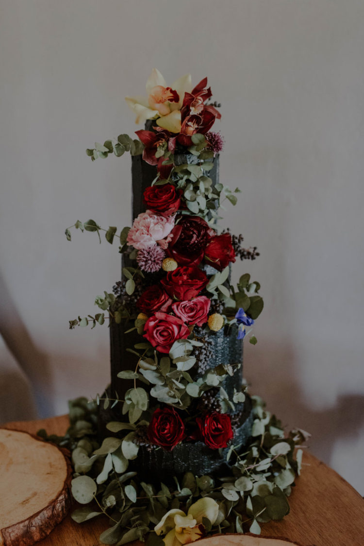 A textural black wedding cake with lush and bright florals was create by the bride
