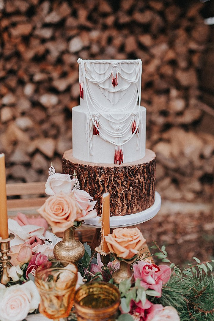 The white wedding cake was decorated with sugar yarn and fringe dipped in red