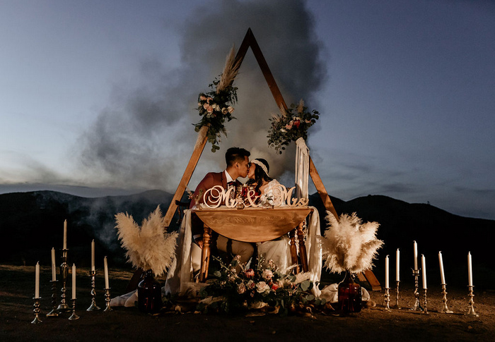 This is a cool sweetheart table idea with a triangle arch, macrame, blooms and pampas grass plus lots of candles