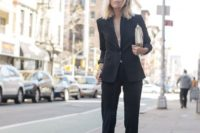 11 a black pantsuit with no top under, a metallic bag and black heels for a sexy look