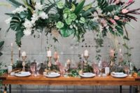 11 a lush tropical wedding installation with tropical leaves and blooms and some cascading greenery