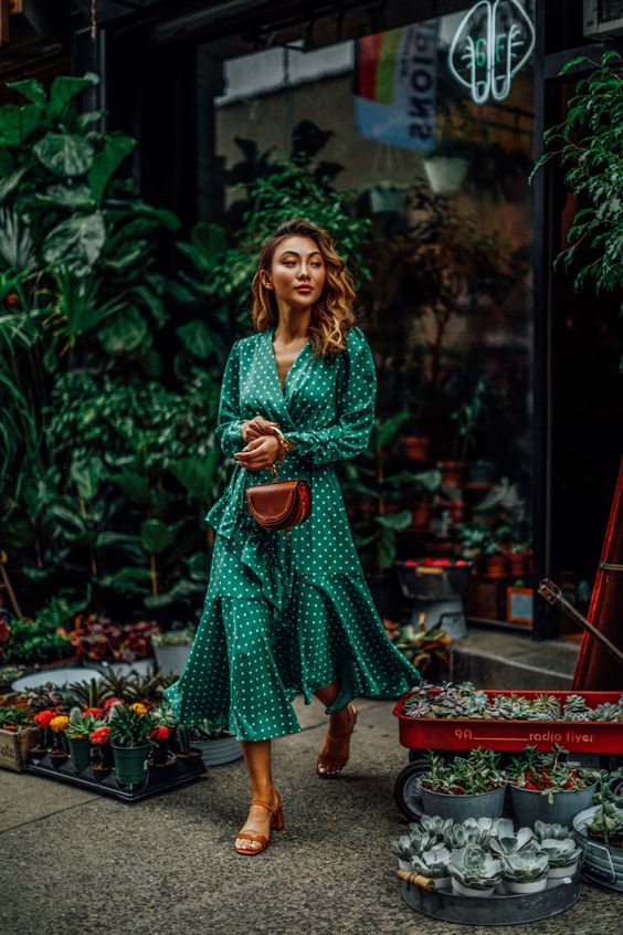 an emerald green wrap midi dress with polka dot prints, brown shoes and a brown bag for spring or summer