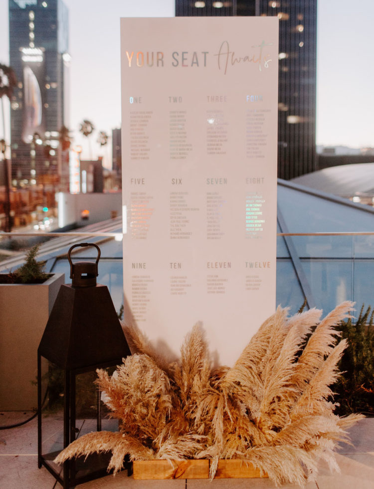 The seating chart was a modern one, decorated with an oversized lantern and pampas grass