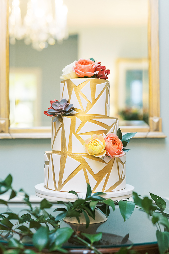 The wedding cake was gold and white, with geometric patterns and bright blooms and succulents