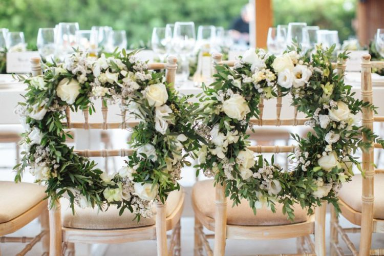 The wedding chairs were decorated with greenery and neutral bloom wreaths